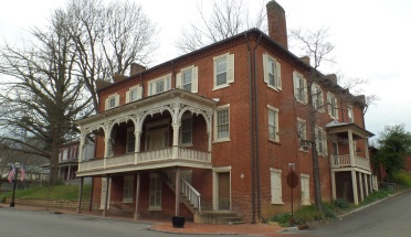 """Built by John W. Simpson around 1843, this was originally called the """"John Simpson Hotel."""" In 1853, Simpson advertised that he had a buggy for sale and asked interested persons to call on him at the """"mansion House."""" The building is still more commonly known as the """"Mansion House."""""""
